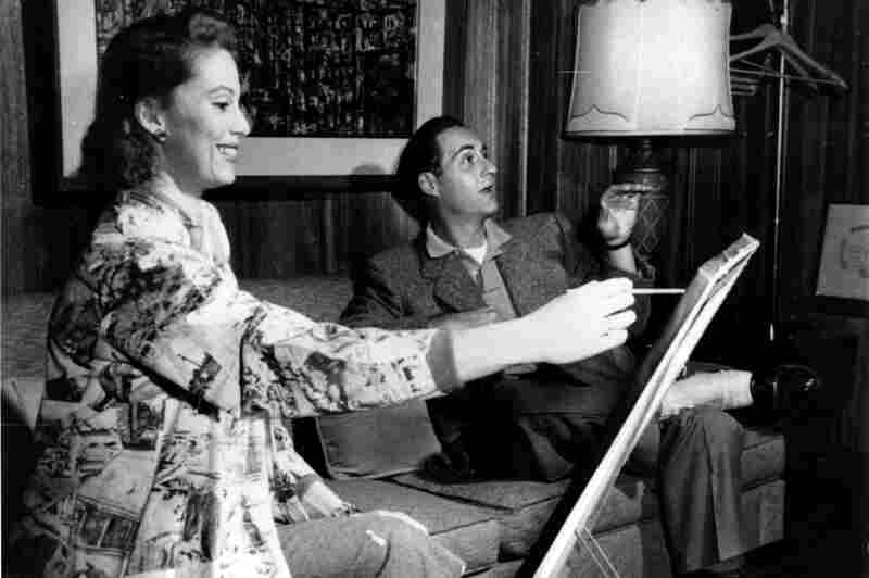 Caesar relaxes while his wife, Florence, paints a portrait of him in their Kings Point, N.Y., home in 1958. Sid's new weekly program, Sid Caesar Invites You, premiered that year.