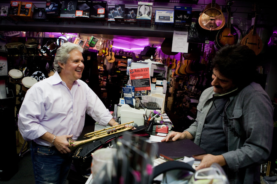 Michael Pagliaro, left, laughs with Paul Scattaretico at the Muzic Store Inc. in Dobbs Ferry, N.Y., as Pagliaro picks up instruments for his rental business. Before Pagliaro had a hip replacement, pain made it difficult to work. (Maggie Starbard/NPR)