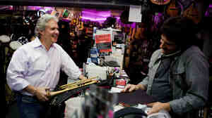 Michael Pagliaro, left, laughs with Paul Scattaretico at the Muzic Store Inc. in Dobbs Ferry, N.Y., as Pagliaro picks up instruments for his rental business. Before Pagliaro had a hip replacement, pain made it difficult to work.