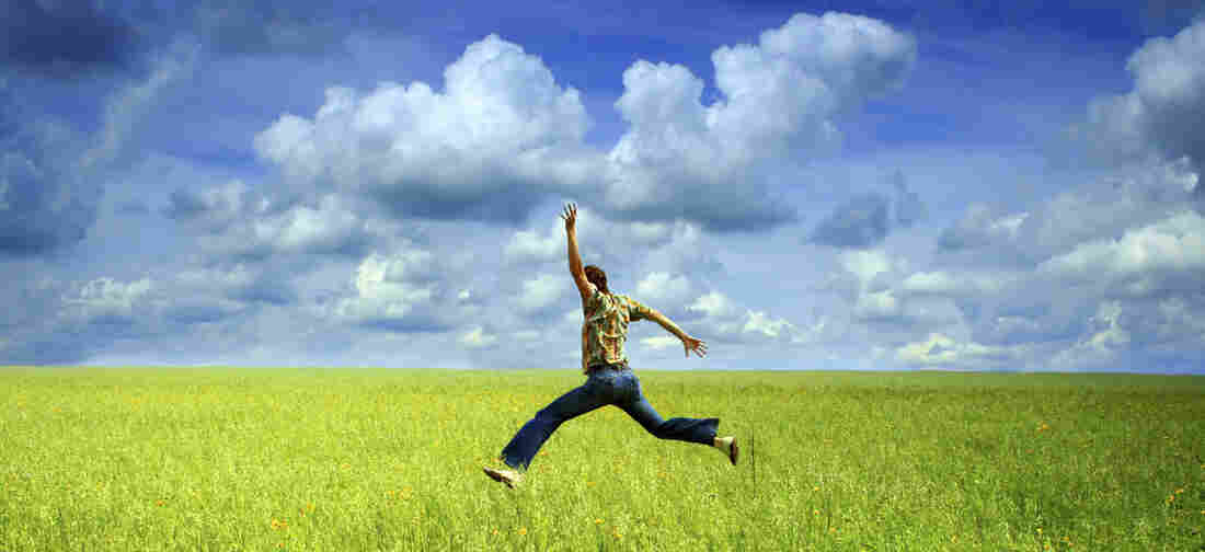 A man jumping in a green field.