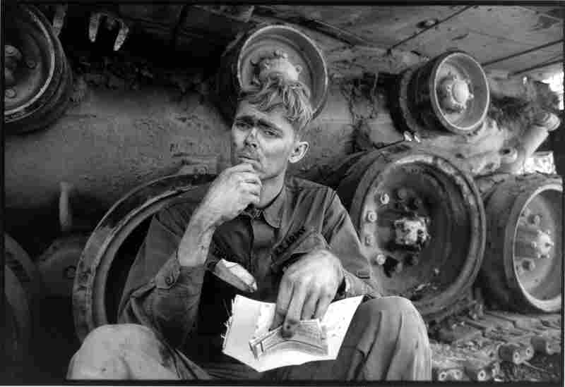An American soldier reads a letter from home while taking a break from repairing a tank tread in Lang Vei, Vietnam, 1971.