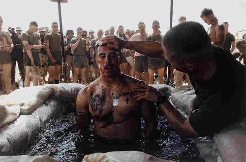 Navy Chaplain Lt. Commander Tom Webber baptizes Cpl. Albert Martinez in a sandbag-lined pool during a ceremony at Camp Inchon, Kuwait, 2003.