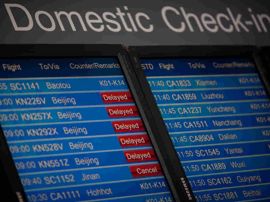 A domestic departures board shows flight delays at Beijing's international airport in January.