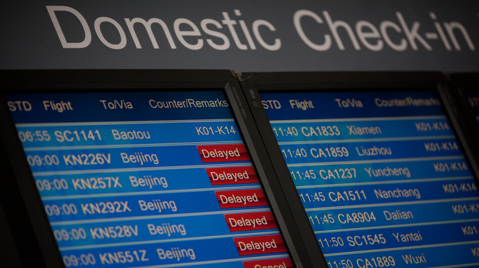 A domestic departures board shows flight delays at Beijing's international airport in January. (AFP/Getty Images)