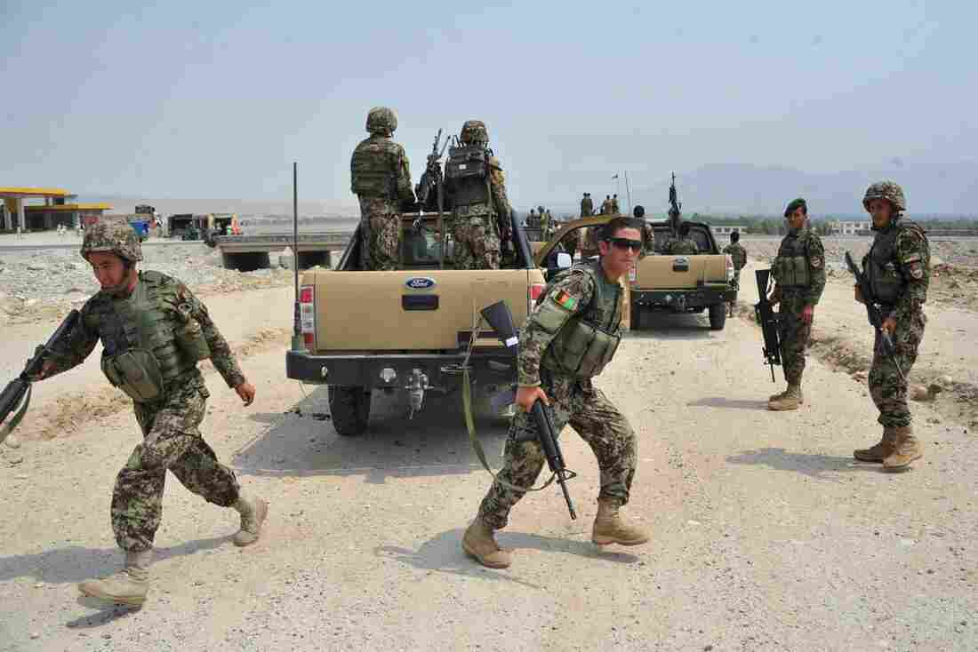 Afghan soldiers take positions following a clash with Taliban fighters on the outskirts of the eastern city of Jalalabad on July 7. The U.S. is trying to organize peace talks, but the latest effort has been put on hold while the fighting continues.