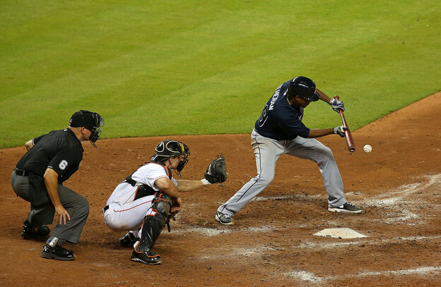 Julio Teheran of the Atlanta Braves bunts during a game against the Miami Marlins at Marlins Park on July 9, 2013 in Miami, Florida.