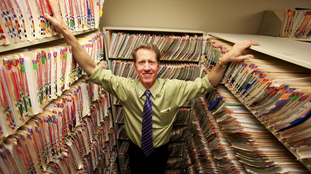 Dr. James Kinsman stands in the practice's records room, surrounded b