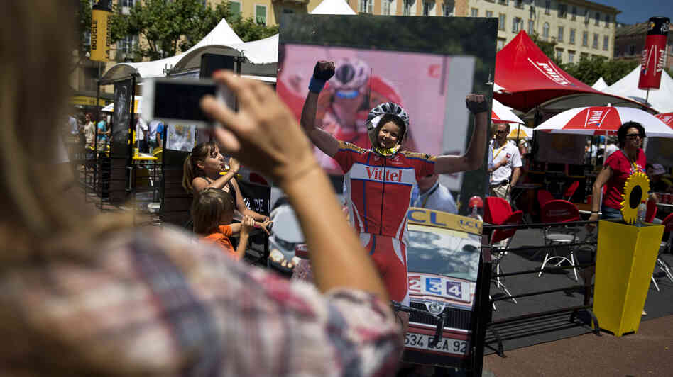 A woman takes a picture of a little girl posing in a cyclist cutout at the 2013 Tour de France. A new petition calls for including women in the epic race.