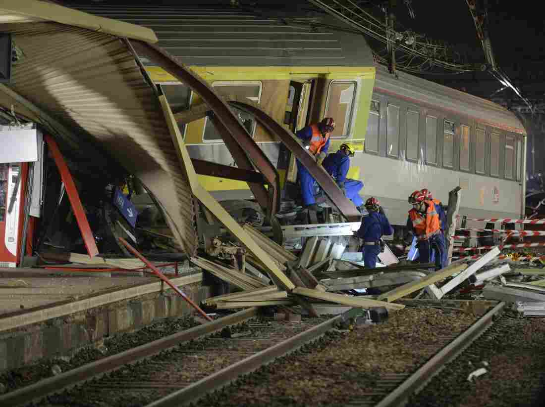 The mangled platform roof and derailed train cars are pictured early Saturday at the site of a train accident at the railway station of Bretigny-sur-Orge, near Paris.