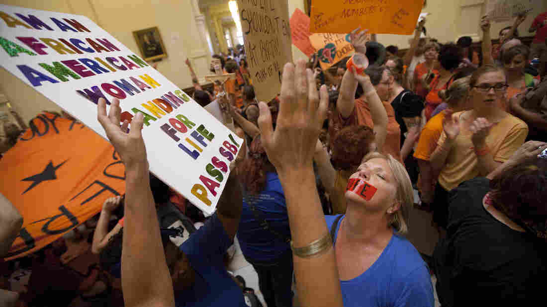 Abortion rights opponents, dressed in blue, and supporters, wearing orange, rally in the state Capitol rotunda Friday before the vote on a set of sweeping abortion restrictions.
