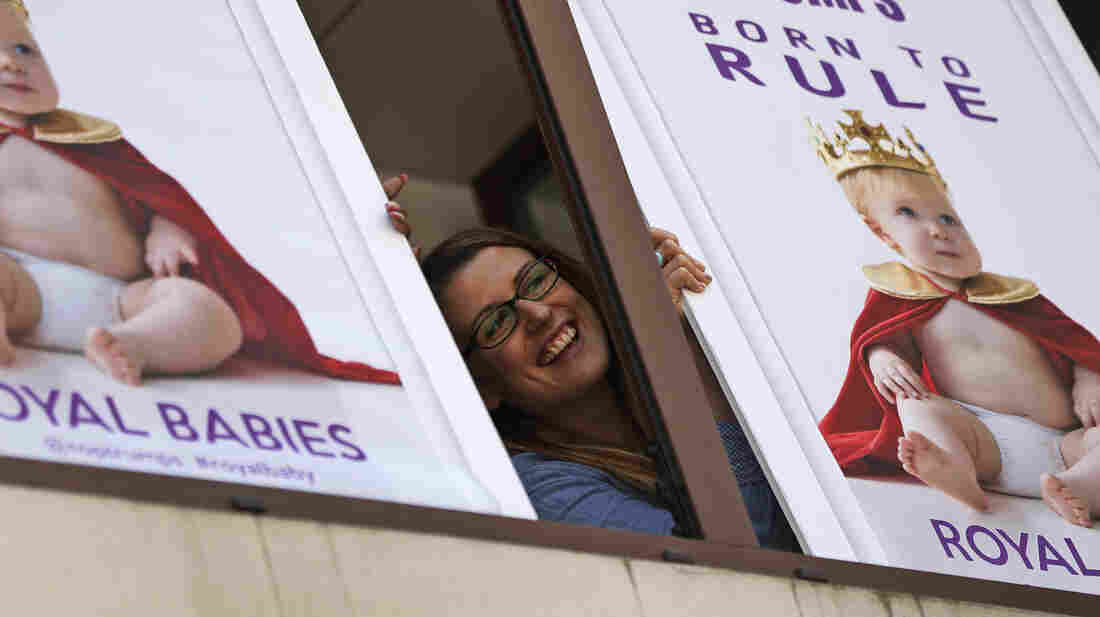"A worker of a games company poses with placards depicting a ""royal baby"" near the St. Mary's Hospital Lindo Wing in London on Thursday. While Buckingham Palace has been mum on the subject, Saturday was rumored to be the official due date for the child who will become the third in line to the British throne."