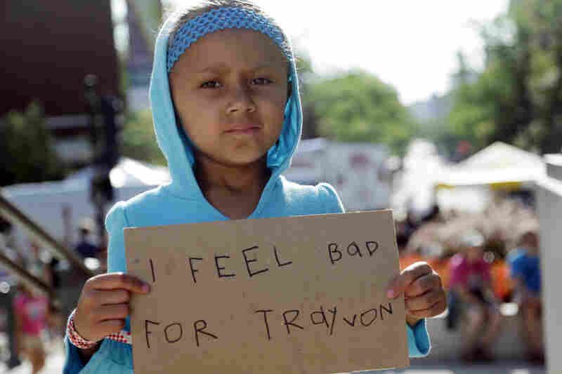 Tatum Stoball, 5, of Madison, Wis., holds up a sign during a protest of the acquittal of George Zimmerman on Sunday in Madison, Wis.