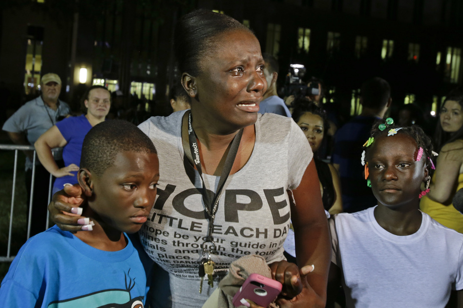 Saturday night, Darrsie Jackson keeps her children — Linzey Stafford, left, 10, and Shauntina Stafford, 11 — close after hearing the not-guilty verdict in the trial of George Zimmerman outside the Seminole County Courthouse in Sanford. (AP)
