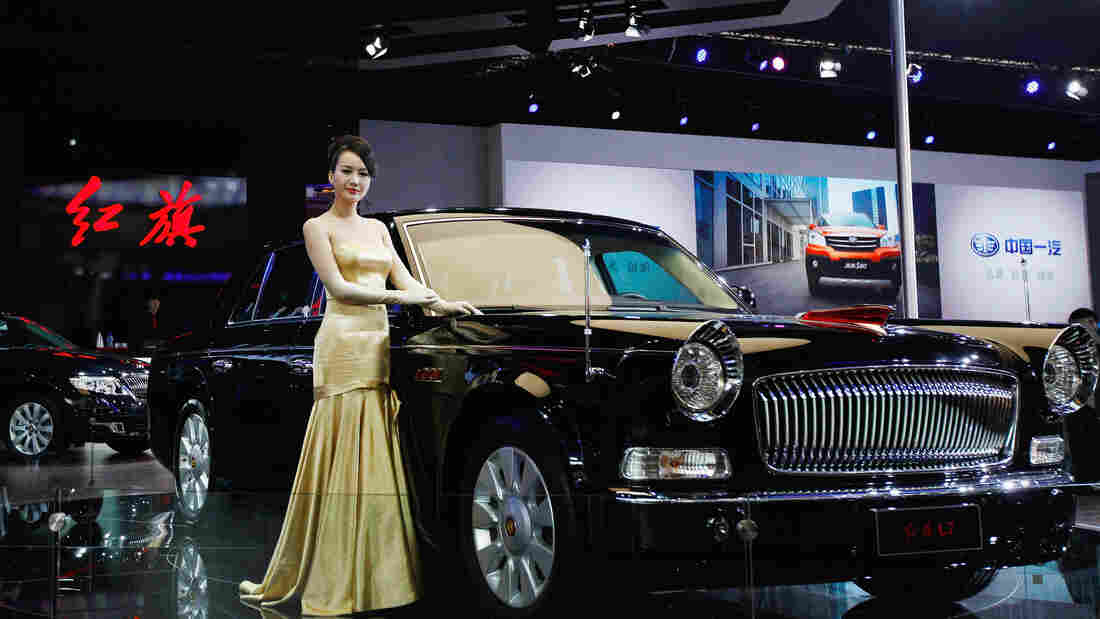 A model stands beside a Red Flag L7 during the 2012 Beijing International Automotive Exhibition in Beijing.