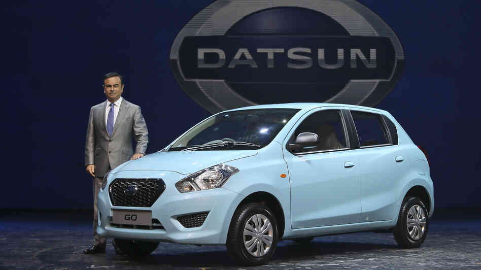 Nissan Motor Co. President and CEO Carlos Ghosn poses with the Datsun Go in New Delhi on Monday. Its the first new Datsun model in more than three decades.