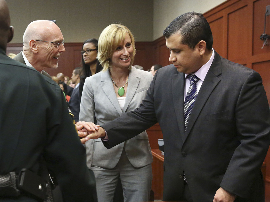 George Zimmerman (right) is congratulated by his defense team Saturday night after being found not guilty of murder in the shooting death of Trayvon Martin. (Gary W. Green/AP)