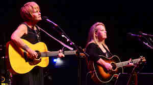 Shawn Colvin (left) and Mary Chapin Carpenter perform together on stage.