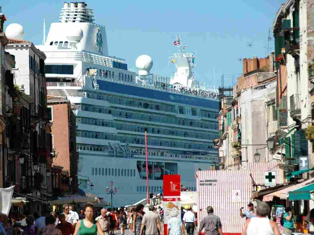 A massive cruise ships towers over Venice. Some 650 cruise ships now visit the Italian city annually, and critics say they threaten the city's fragile architecture.