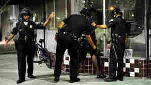Los Angeles Police Department officers in riot gear detain a man after disturbances in the streets around Leimert Park.
