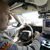 An Arizona Department of Public Safety officer keeps an eye on his dashboard computer as it reads passing car license plates.