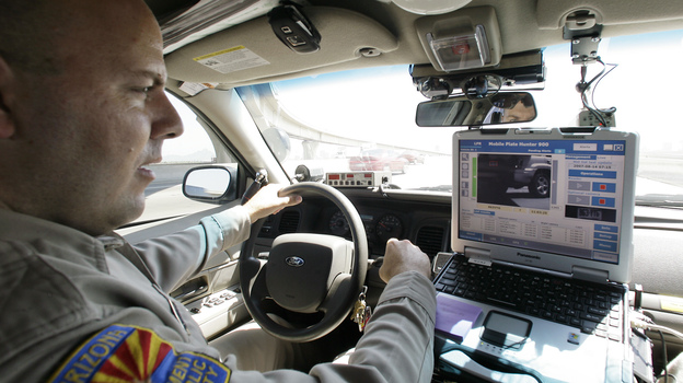 An Arizona Department of Public Safety officer keeps an eye on his dashboard computer as it reads passing car license plates. (AP)