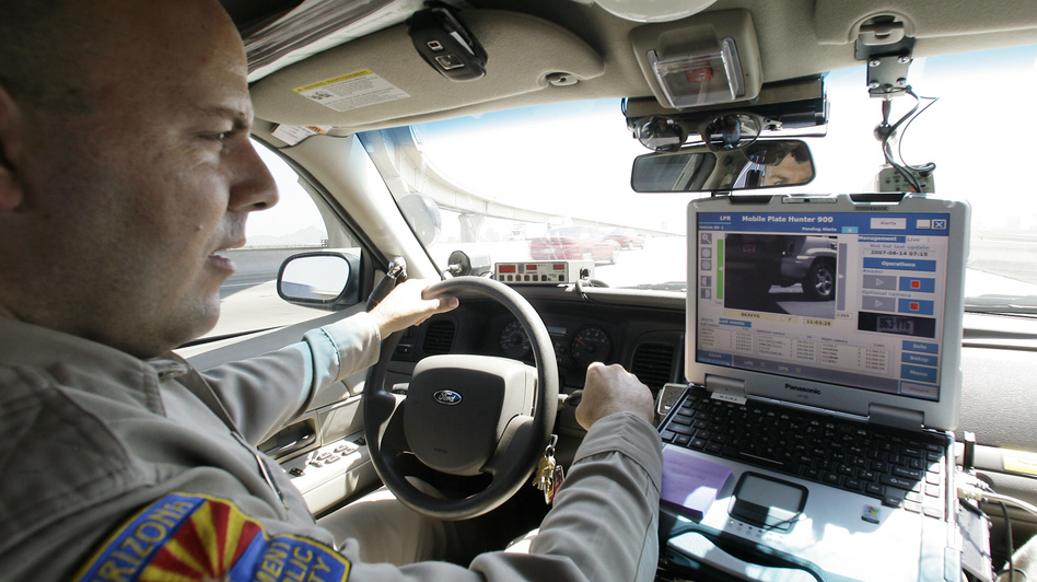 An Arizona Department of Public Safety officer keeps an eye on his dashboard computer as it reads passing car license plates. (Ross D. Franklin/AP)