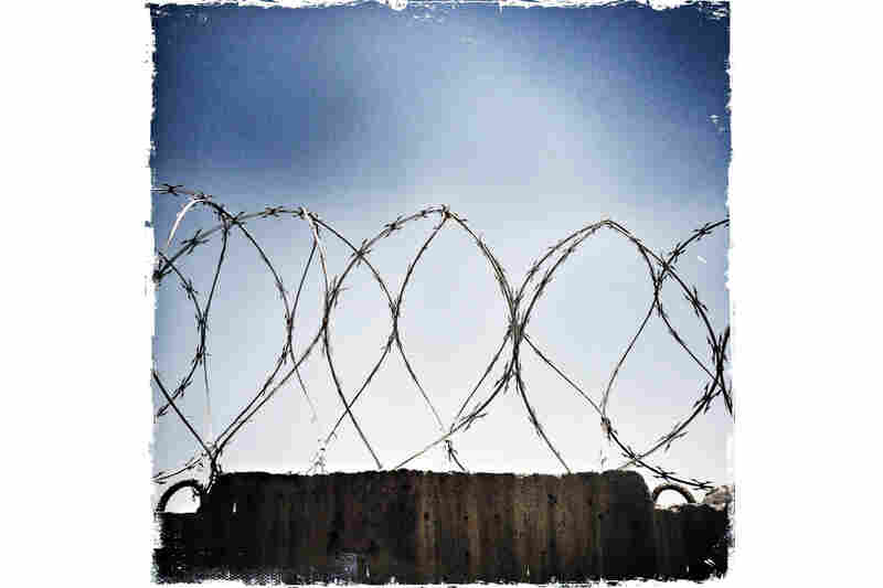 Razor wire tops almost every wall separating the bases from the local Afghan population.