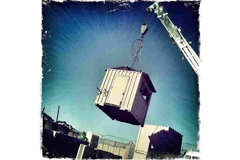 A guard tower is moved back to the inner perimeter of a small base outside Kandahar. If the bases are not being closed permanently they are being scaled back to accommodate fewer soldiers when the Afghans take over.
