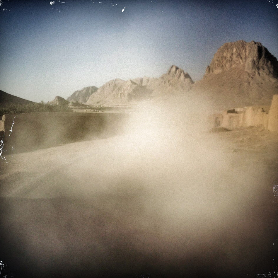 "Dust rises behind a convoy traveling down a dusty road near Kandahar. Soldiers refer to their backside as ""their six"" as in 6 o'clock: or, when facing ahead at 12, the area that's behind."