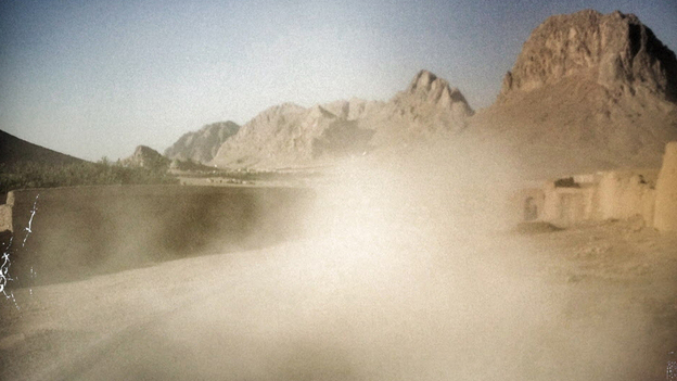 """Dust rises behind a convoy traveling down a dusty road near Kandahar. Soldiers refer to their backside as """"their six"""" — as in 6 o'clock: or, when facing ahead at 12, the area that's behind. (NPR)"""