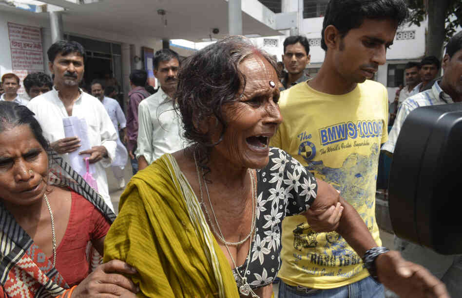 A woman cries after her grandson, who consumed a poisoned meal at a school on Tuesday, died at a hospital in the eastern Indian city of Patna.