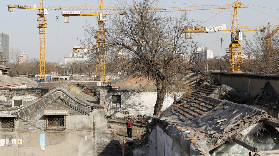 A woman in Beijing stands amid houses being demolished for new residential town, on Feb. 27.