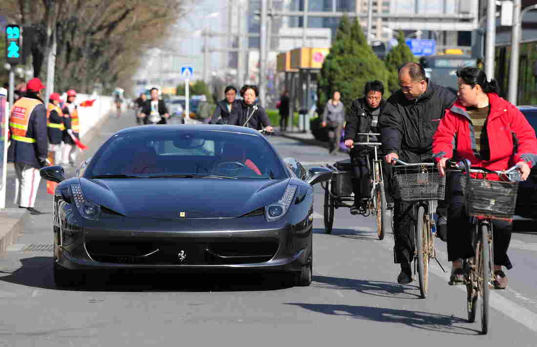 Cyclists look at a Ferrari parked illegally and blocking the bicycle lane off a main road in Beijing, on April 7, 2011.