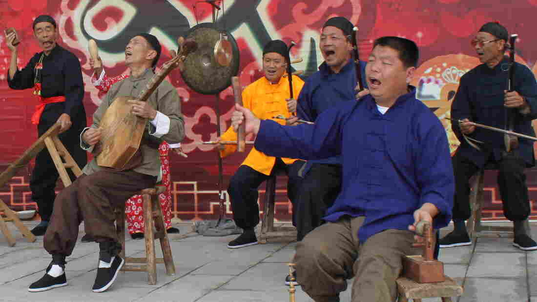 "Zhang Junmin (second from right) and his band perform the Lao Qiang music special in northwest China's Shaanxi province. The character behind the stage means ""drama""; Lao Qiang music used to accompany puppet plays and includes a strong storytelling component."