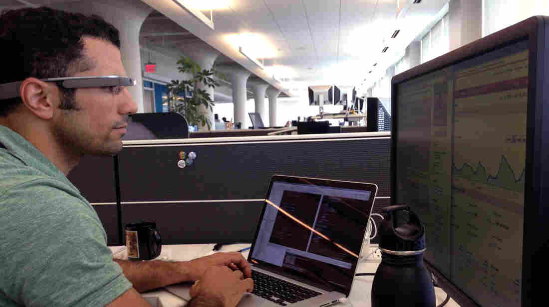 NPR developer Michael Seifollahi wears Google Glass while working at his desk.