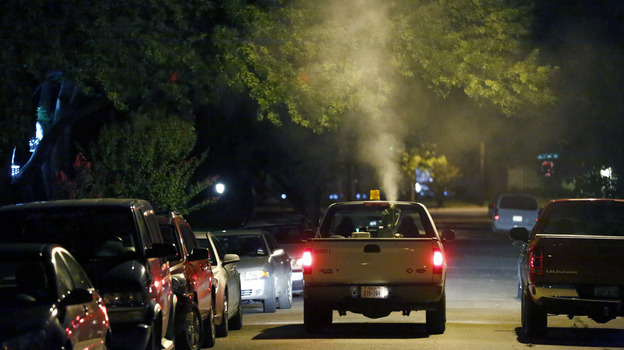 A sprayer truck blankets a neighborhood in North Dallas with insecticide to curb mosquitoes carrying West Nile virus in July 2012. (Corbis)