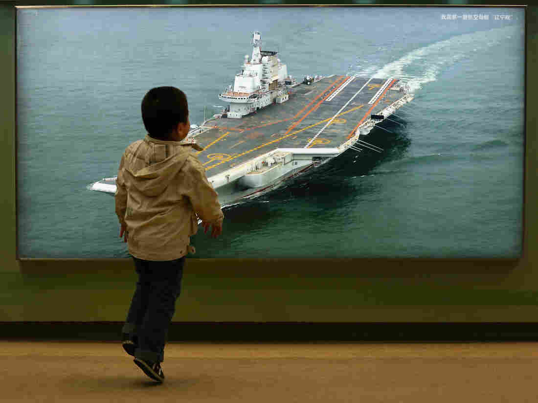 """A Chinese boy passes a photo of China's first aircraft carrier during an exhibition entitled """"Scientific Development and Splendid Achievements"""" in Beijing in 2012."""