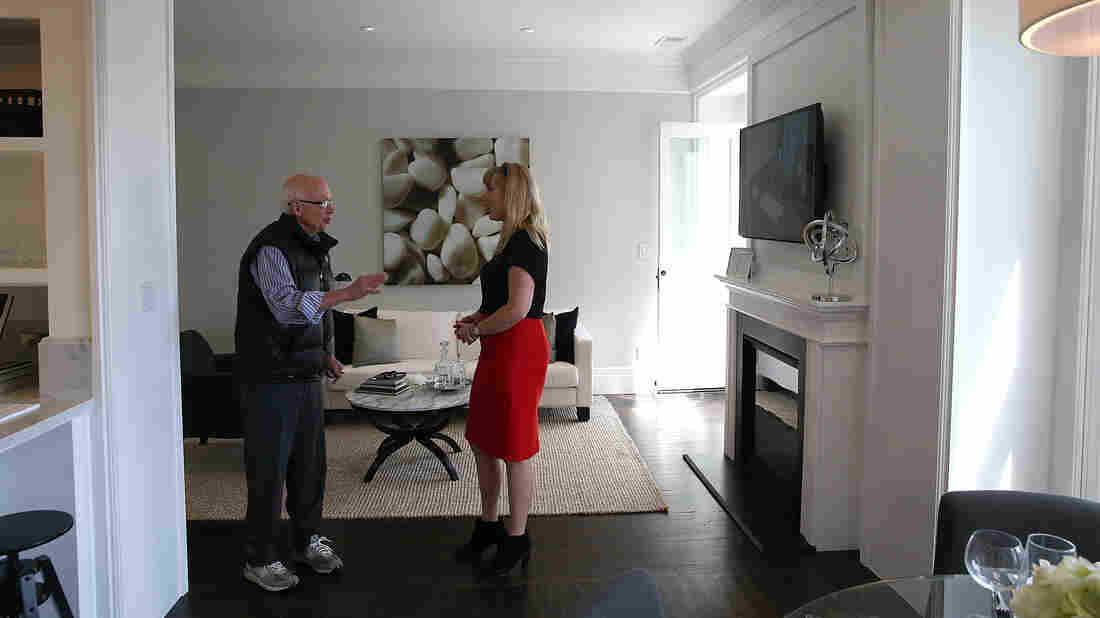 Real estate agent Katie Hayes (right) answers questions about a home for sale during an open house in San Francisco in May. With the median home price now in excess of $1 million, many longtime residents feel squeezed out.