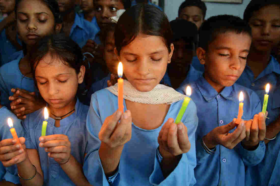 Indian school children hold candles as they pay tribute to school children who died from food poisoning in Saran district of Bihar state.