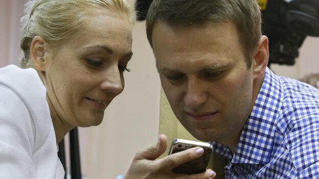 Russian opposition leader Alexei Navalny and his wife, Yulia, look at a mobile phone Thursday during his trial in Kirov, Russia. A Russian judge found Navalny guilty of embezzlement.
