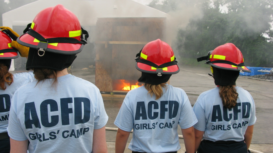 Girls at the Arlington County, Va., fire camp watch a staged fire. Firefighters hope to encourage the teenagers to consider the fire service as a career. (NPR)