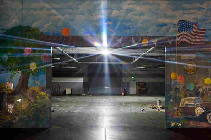 A single light shines inside the service center of a closed dealership.