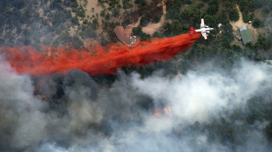 An aircraft lays down a line of fire retardant between a wildfire and homes in the dry, densely wooded Black Forest area northeast of Colorado Springs, Colo., on June 13.