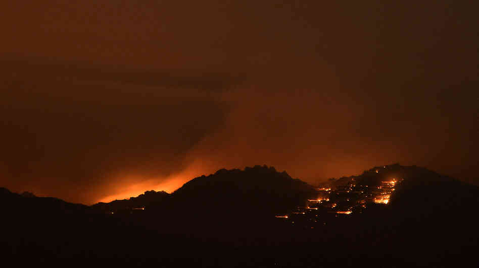 Fire lights the sky near Idyllwild, Calif., early Thursday. Flames have spread close to Palm Spring