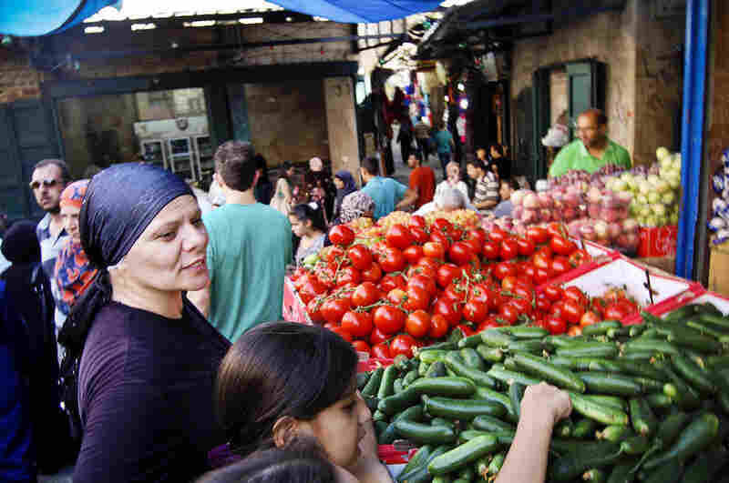 Jehad Outteineh shops at a market near the Damascus gate in the Muslim quarter of Jerusalem's Old City. Around the world, hundreds of millions of Muslims are fasting from sunrise to sunset during Ramadan. Outteineh is shopping for the family's iftar, the meal that breaks the fast.