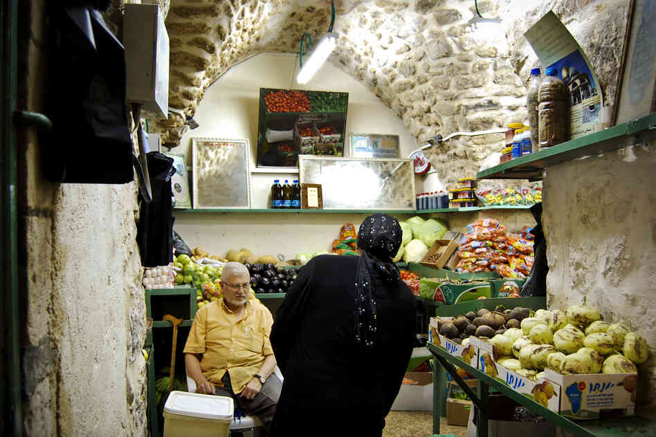 Outteineh ducks into a produce shop off the main walkway, in the Muslim quarter.