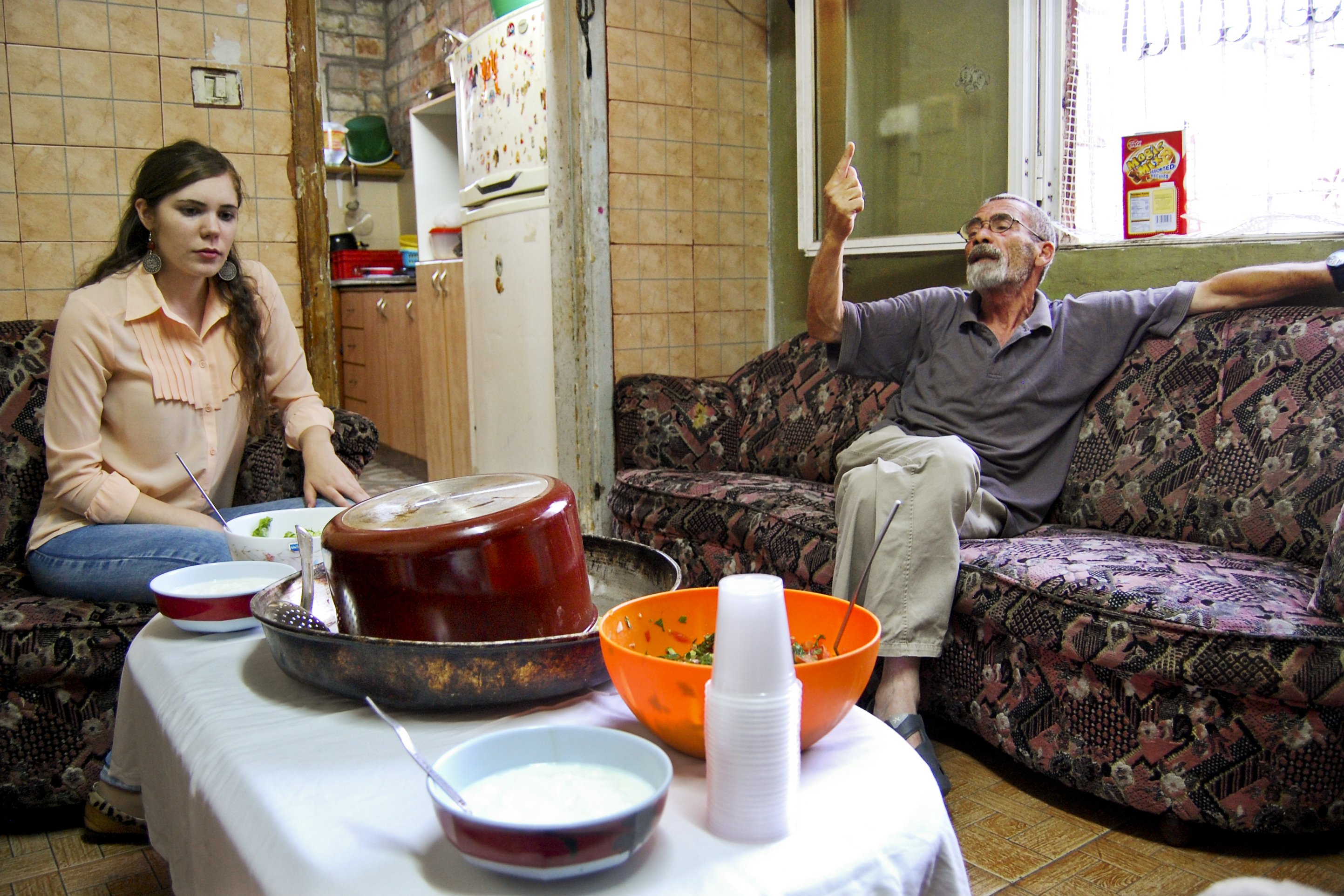 Outteineh's daughter Hiba, 21, and husband, Hattim, talk in the family's living room as sunset nears. The maqluba pot (center) is turned upside down in the serving dish, a trick to keep it warm until the Ramadan fast can be broken.