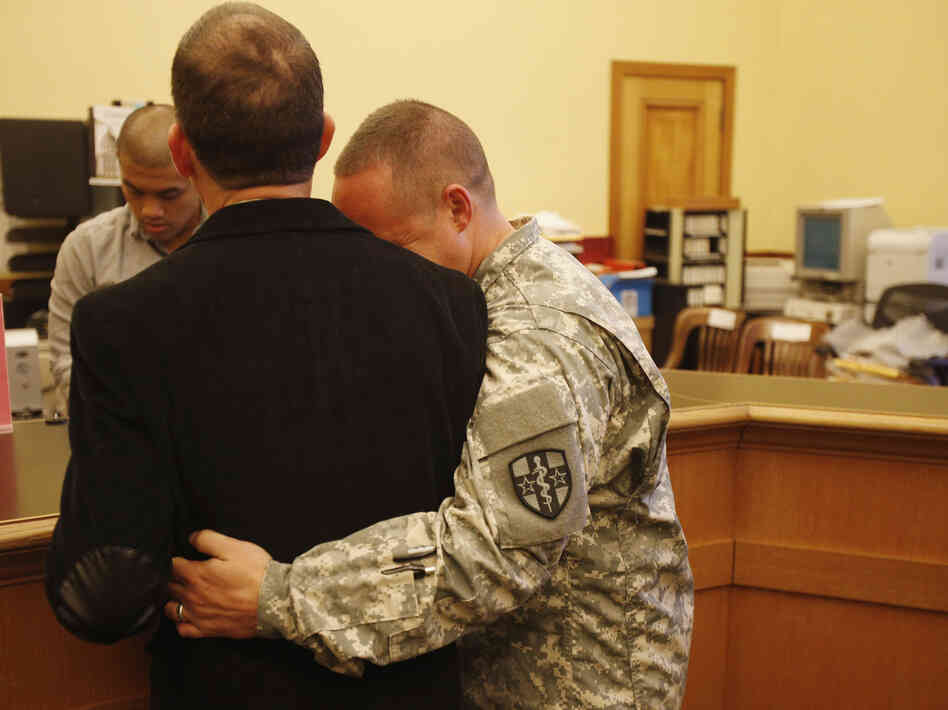 U.S. Army Captain Michael Potoczniak (right) embraced his partner of 10 years Todd Saunders as they obtained their marriage license at City Hal