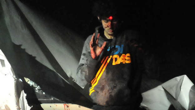Boston bombings suspect Dzhokhar Tsarnaev on April 19 as he emerged from a boat stored in a Watertown, Mass., backyard. The red dot of a police sharpshooter's laser sight can be seen on his forehead. (Boston Magazine)