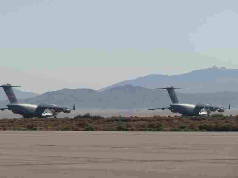 "A pair of C-17 Globemaster IIIs on the ground at Edwards Air Force Base in California, where ""vortex surfing"" is being tested."